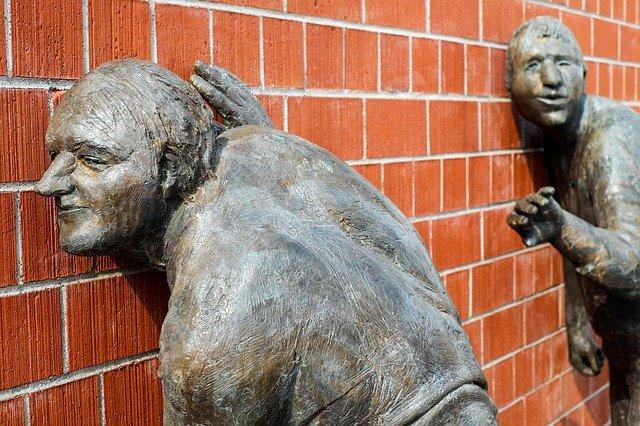 פסל של אדם מאזין בסתר מעבר לקיר